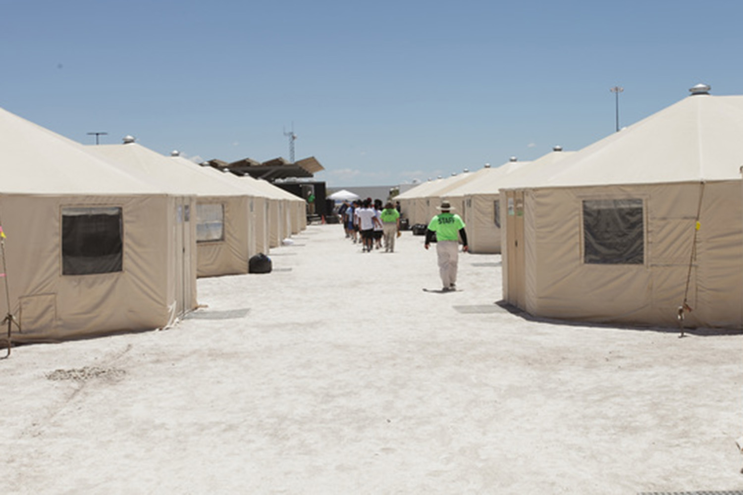 Staff accompany children inside the tent city at Tornillo, near El Paso, where undocumented immigrant minors are being held by the federal government.