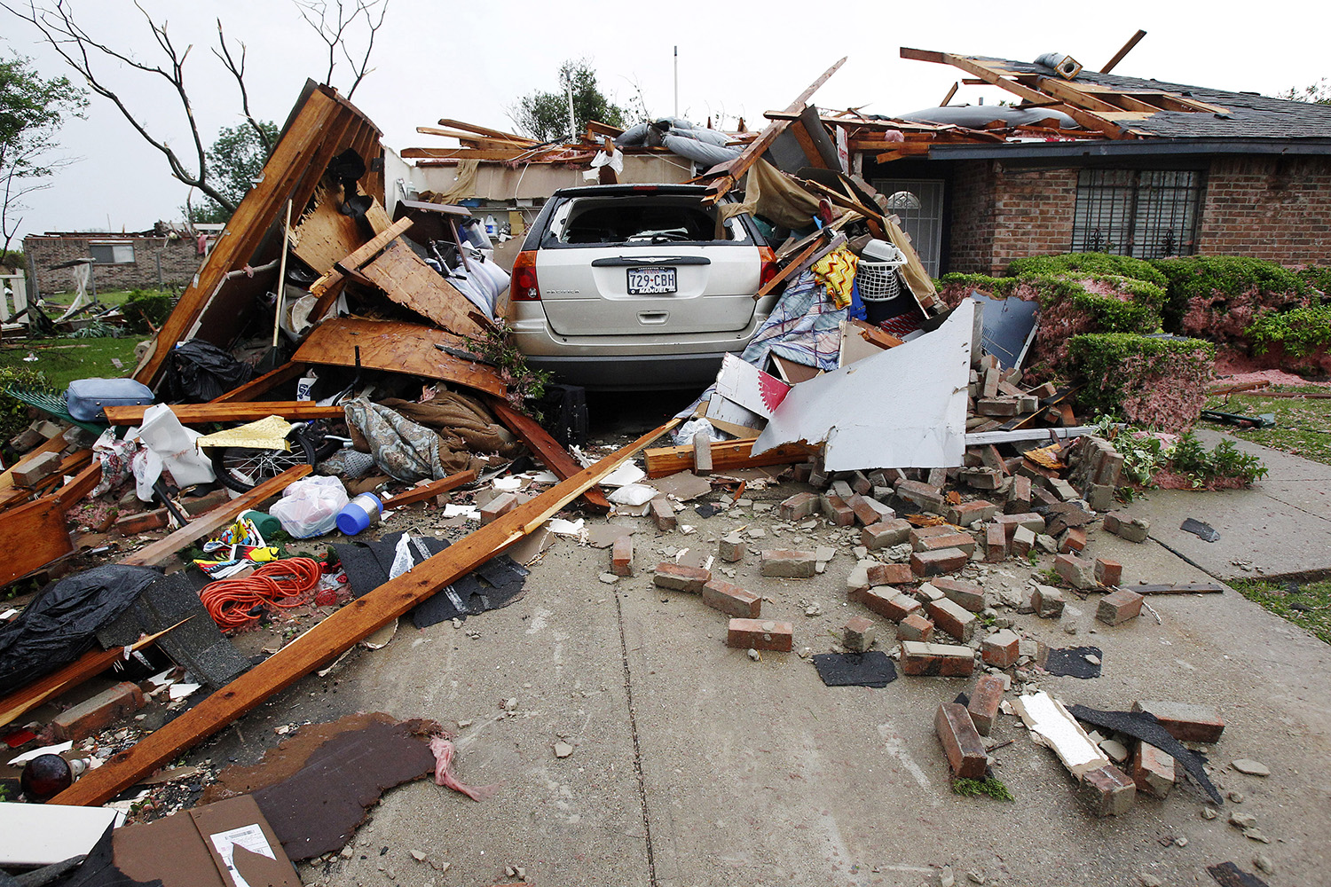 A vehicle rests in the driveway of a home destroyed by a series of tornadoes ripping through the Dallas suburb of Lancaster on April 3, 2012. Up to a dozen tornadoes skipped through the densely populated Dallas-Fort Worth area, ripping apart homes and tossing tractor-trailer trucks into the air, but there were no reports of serious injuries or deaths.