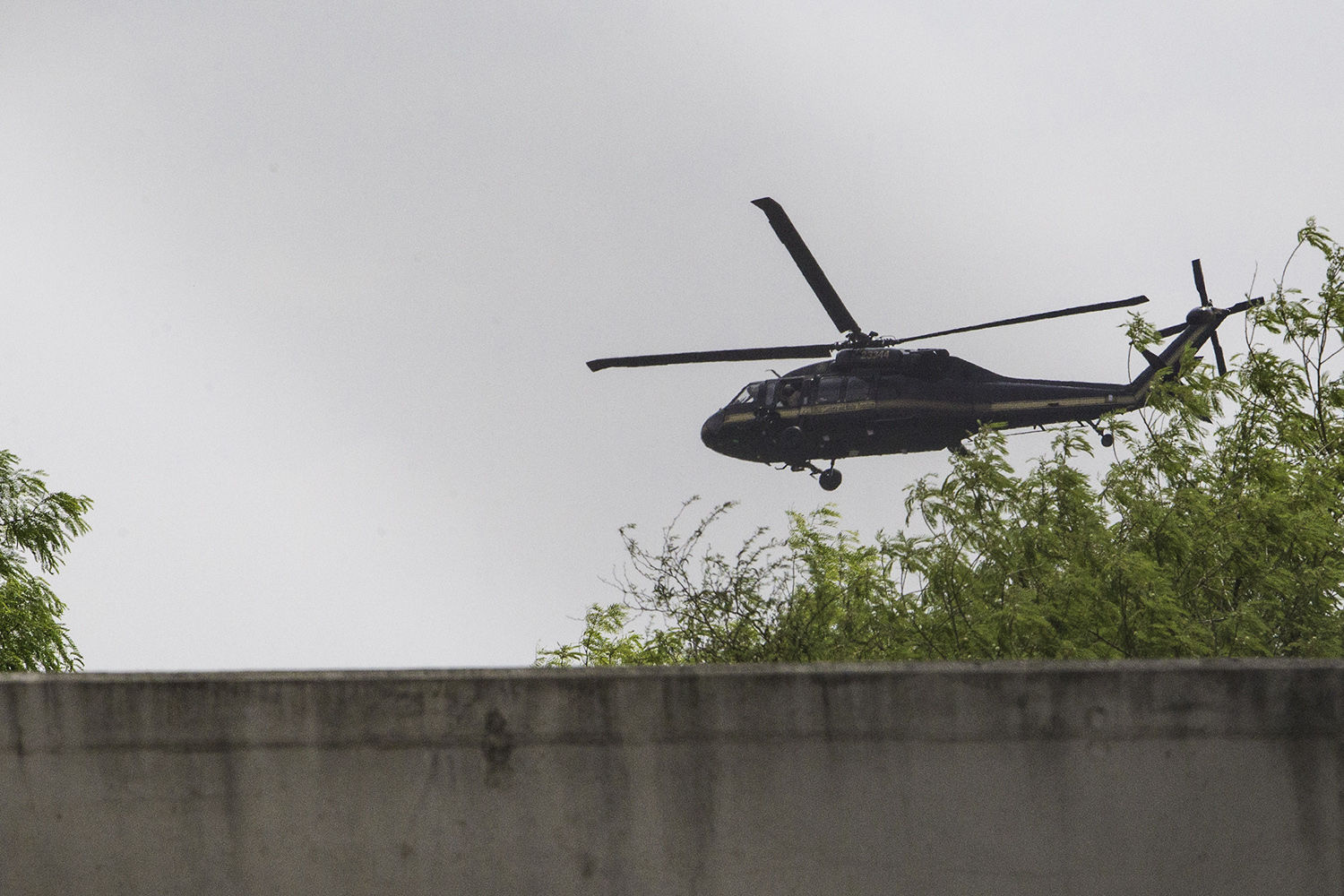 A Department of Homeland Security Blackhawk helicopter flying near Hidalgo, swoops low over the Rio Grande above the border wall built in 2008.