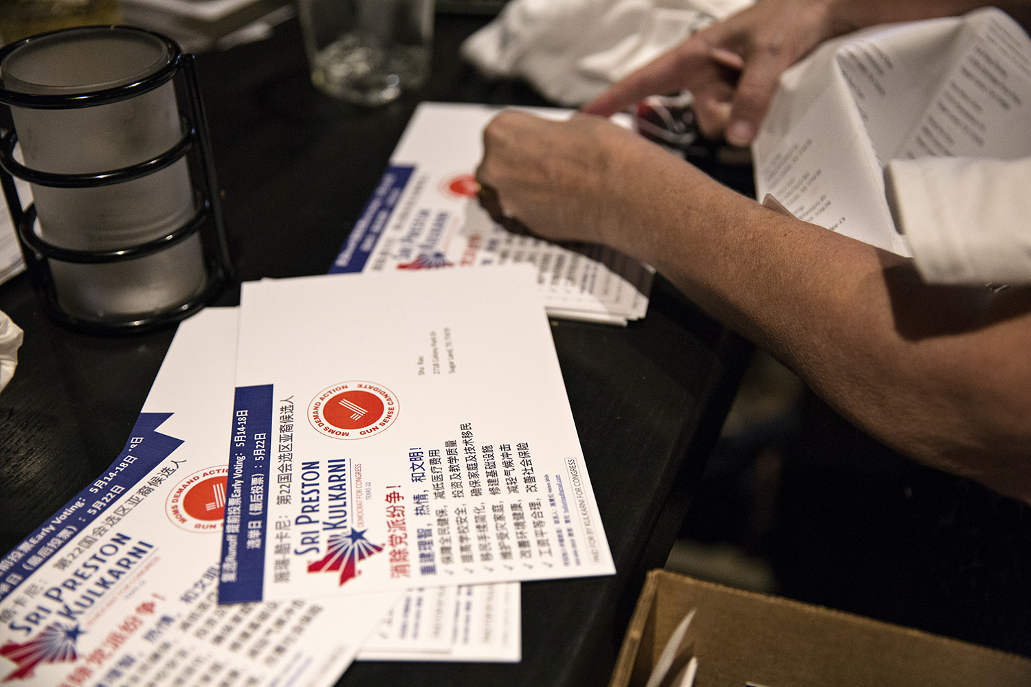 Campaign volunteers of Sri Preston Kulkarni place address labels on postcard mailers written in Mandarin Chinese.