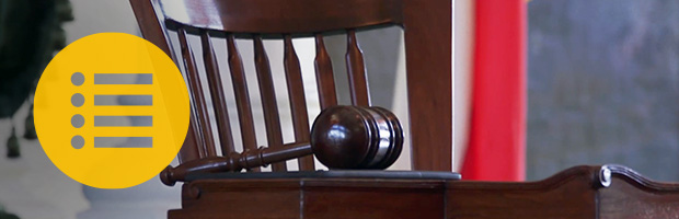 Gavel resting on table with menu symbol overlaid.