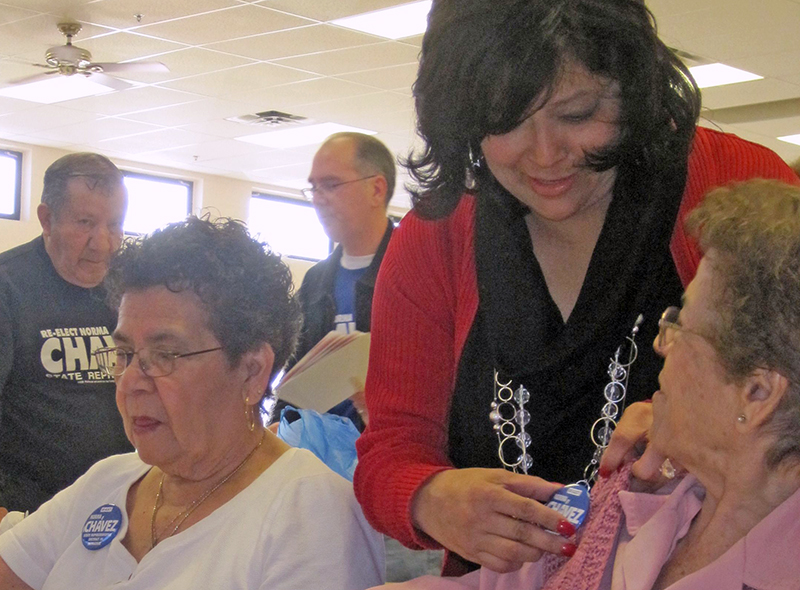 Norma Chavez works attaches a campaign button to the sweater of one of her supporters at an El Paso senior center before the 2010 Democratic primary election.