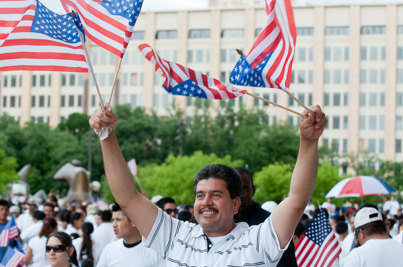 Demonstrator Jesus Sandovar waves four American flags at an immigration rally in Dallas.