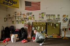 William Crow, 41, who did two years for drug possession, crouches in the shop adjoining the bus station where recently released inmates are buying new clothes, shoes and cigarettes in Huntsville, Texas on March 4, 2011.
