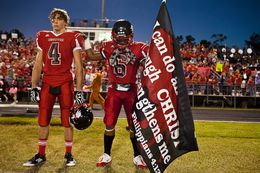 As two Kountze football players prepare to play a game on Oct. 5, 2012, one holds a banner with a Bible verse. A Hardin County judge recently ruled that the high school's cheerleaders can continue to display signs with religious messages at football games.