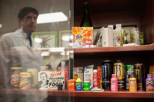Recalled products, natural threats, choking hazards, and items that could cause emergencies when large amounts are ingested by children, are displayed at the South Texas Poison Center in San Antonio. Miguel Fernández, managing director of the center, is reflected in the display case glass.