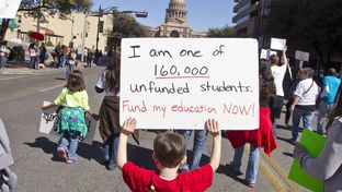 A kindergarten-age schoolboy walks up Congress Ave for a Save our School's rally on February 23rd, 2013