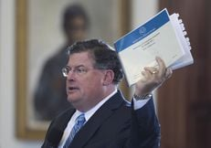 Senate Finance Chairman Tommy Williams, R-The Woodlands, holds a copy of the state budget on the Senate floor March 20, 2013.