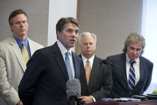 Gov. Rick Perry announces a 5 percent cut in the Texas franchise tax for small business on April 15, 2013. In the background are Rep. Harvey Hildebran, R-Kerrville, Gary Farmer of the Austin Chamber and MIke Morrissey of the governor's staff.