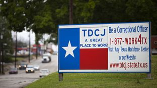 A sign outside of the Texas Department of Criminal Justice Headquarters in Huntsville. Last year, Texas prison officials approved a $3,000 bonus for correctional officers in units where a boom in oil and gas jobs has made it hard to find new hires. They are currently working with state lawmakers to grant all correctional officers a 5 percent pay increase.