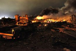 A vehicle near the remains of a fertilizer plant burning after an explosion in West, Texas, near Waco.