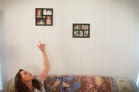 Megan Winfrey, 25, points at photos of her daughter Danielle Hammond, 7, in her mobile home in Coldspring, Texas, Thursday, May 23, 2013. Megan Winfrey was released from prison after being acquitted of murder earlier this year. The court said that the dog-sniff evidence used to secure her conviction was insufficient.