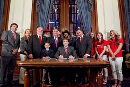 Gov. Rick Perry signs House Bill 308 which allows public school students and staff to use traditional holiday greetings and display religious symbols on school property. He was joined by bill author Rep. Dwayne Bohac R-Houston, Bahac's  son Reagan, Sen. Robert Nichols as well as several Santa's, Rabbi Zev Johnson and cheerleaders from Kountze High School - June 13, 2013.