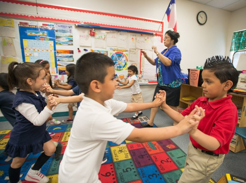 "Pre-K teacher Josefina Pineda teaches her students the concept of ""push"" by having them join hands and push back and forth in her classroom at the Dallas Independent School District elementary school Cesar Chavez Learning Center in 2013."