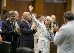 Sen. Wendy Davis, D-Ft. Worth, waves to the gallery while leaving the Senate chamber after midnight on June 26, 2013.
