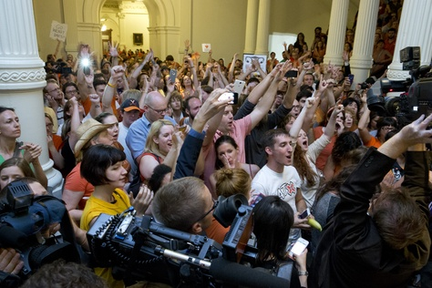Protesters outside the Texas Senate chamber cheer as Sen. Wendy Davis leaves on June 26, 2013.