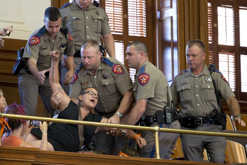 A protester who yelled out during the final vote on HB 2 the abortion bill is removed from the House gallery on July 10, 2013.