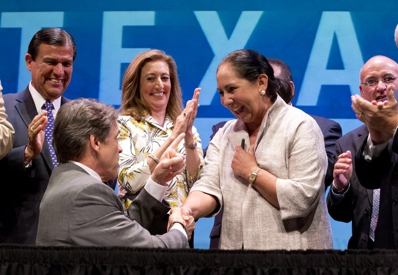 Gov. Rick Perry and Juliet García of the University of Texas at Brownsville at a signing ceremony on July 16, 2013, for the merger of UT-Brownsville and UT-Pan American.