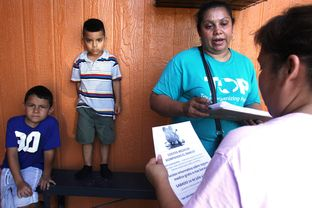 Zoila Chaver, second from right, a member of the Texas Organizing Project, giving health care information to Dallas resident Graciela Garcia at Garcia's home on July 10, 2013.