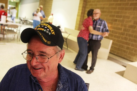 David Rockwell, 64, a Navy Vet who served in the Vietnam War, laughs with friends while other participants in the family night gathering dance in the background. The family night was put on by the Military Veteran Peer Network and held in Palestine, TX, Aug. 3, 2013.