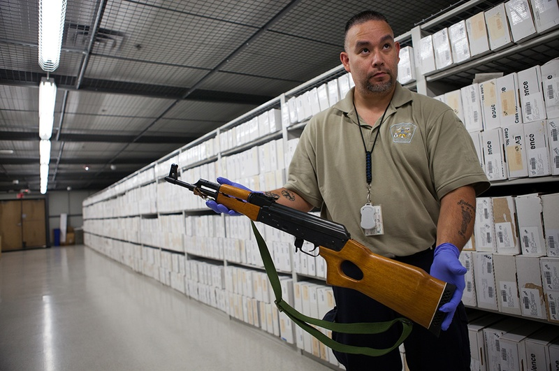 Evidence Specialist, Richard Castro, shows a firearm held as evidence by APD. The Austin Police Department's evidence and seized property storage facility contains thousands of firearms from handguns to assault rifles dating back as far as the 1970s.