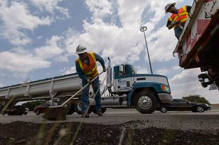 TxDOT employees Brad Shepard and Canaan Johnson finish up after putting asphalt cold mix down for edge repairs on Interstate 35-S near Parmer Lane on Monday August 19th, 2013.