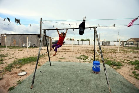 A young girl plays outside her home in the Pueblo de Palmas colonia near Mission, Texas, on Aug. 29, 2013.