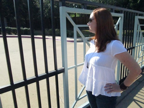 Cadence King of Bryan stands at the gate of the now closed Bryan Planned Parenthood clinic.