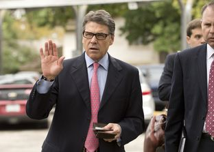 Gov. Rick Perry holds his Texas driver's license and his wallet as he heads to a west Austin early voting site on October 30, 2013.
