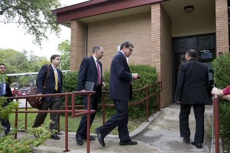 Aides follow Gov. Rick Perry into a West Austin early voting station on Oct. 30, 2013.