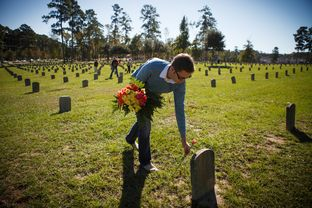 Anthony Ormsbee places flowers with other volunteers at the Texas Department of Criminal Justice's Captain Joe Byrd Cemetery in Huntsville, Texas Monday Nov. 4, 2013 where a group placed roses on the more than 3000 headstones for All Souls Day.