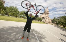 Carlos Gutierrez holds up his bike in front of the Texas Capitol on November 9th, 2013 after a 12 day bike ride across Texas.