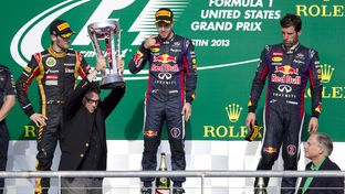 Then-Gov. Rick Perry hoists the Formula One U.S. Grand Prix trophy on November 17, 2013, with Attorney General Greg Abbott watching on.