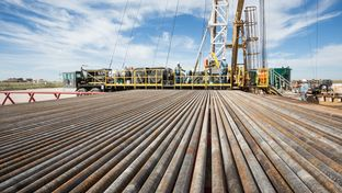 Pipes used for fracking are shown in front of a Fasken OIl and Ranch drilling rig outside of Midland on Oct. 8, 2013.