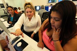 Lindsay Berlanga, center, site manager for Cognazante, helps Melissa Villareal, right, and her mother, Hortensia Villareal, rear, with registration for the Affordable Care Act during assistance hours at Bibliotech, the new digital public library in San Antonio, Friday, January 17, 2014.