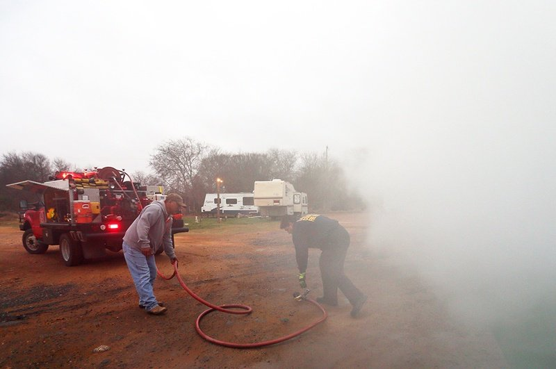 Part time senior fire fighter Richard Prado responds to a radio call about a dumpster fire at Pat's RV Park on Main St in Cotulla, a man camp that houses oil field workers, during his 24 hour shift at the La Salle County Fire Department, Thursday, January 23, 2014. Park owner Pat Niaves assists him with the hose since he is working the shift alone.