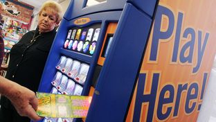 Dawn Nettles, who runs the lottery watchdog website lottoreport.com, stands by a scratch-off display in Mesquite.