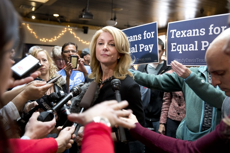 Wendy Davis listens to a press question at Scholtz Garden on March 24, 2014 following an equal pay rally.