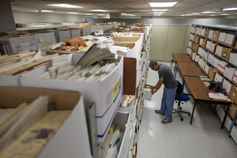 """Daniel Ortuño, who manages the 1.5 million drilling records stored at the University of Texas at Austin's Bureau of Economic Geology, examines well data in what he calls the """"spooky room,"""" home to thousands of records that he has not yet organized. State water researchers are using information from some logs to map potential water sources."""