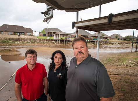 Granbury resident Joe Williams (left) stands with City Council Member Rose Myers and Hood County Commissioner Steve Berry under a Lake Granbury resident's dock in the Waters Edge neighborhood on Lake Granbury's north shore. The lake is 53 percent full.