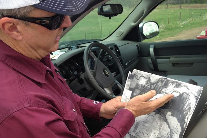 Tommy Henderson shows a survey of land along the Red River in North Texas.