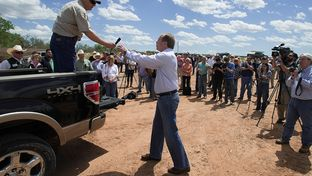 Lt. Gov. David Dewhurst accepted the microphone from Texas landowner Tommy Henderson on April 28, 2014, during a gathering of politicians, landowners, law enforcement officials and news outlets on Red River land northeast of Byers, Texas. Dewhurst expressed support for ranchers in their fight with the BLM over land they say they own.