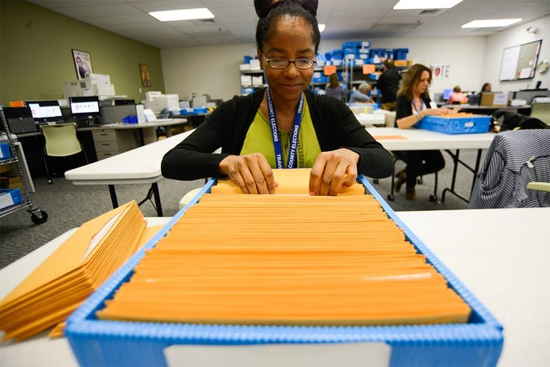 Ballot-by-mail clerk Chaundra Grattan organizes ballot packages at the Travis County Elections Division in Austin on May 19, 2014.