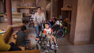 An aid worker and Aaron Sanchez, who is 3 years-old and has Gastaut syndrome, walk through the living area of the Los Ojos de Dios Center on June 3, 2014 in Juarez, Mexico. The center opened in 2008 and serves special needs children who are orphans.