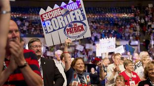 Delegates wave Dan Patrick posters advocating a more secure border on the Texas Republican Convention floor on June 7, 2014.