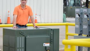Chris Schein of Oncor stood with one of the company's new batteries at Oncor's Environment System Operating Services Facility near Lancaster on June 12, 2014.