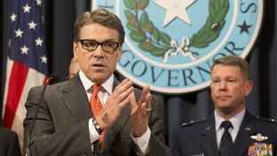 Gov. Rick Perry announces the deployment of National Guard troops along the Texas border as Texas Guard Adjutant General John Nichols listens at the Texas Capitol on July 21, 2014.