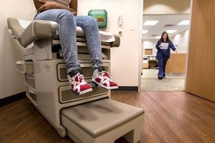 Eighth-grader Montanique DeShay waits as Ashlyn Brooks, medical assistant at MedSpring Urgent Care in Austin, comes to check on her on Wednesday. Like many patients visiting urgent care facilities at this time of year, Montanique is having a physical evaluation performed to allow her to participate in sports this school year.