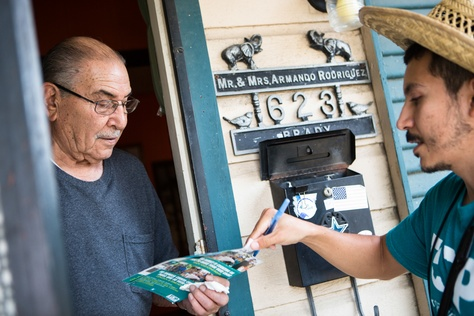 Chris Ornelas, a Texas Organizing Project employee, speaking with Armando Rodriguez while canvassing in San Antonio's west side on Sept. 4, 2014.