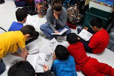 A reading assistant reads on the classroom floor with a small group of fourth graders at Wanke Elementary School in San Antonio on March 9, 2012.